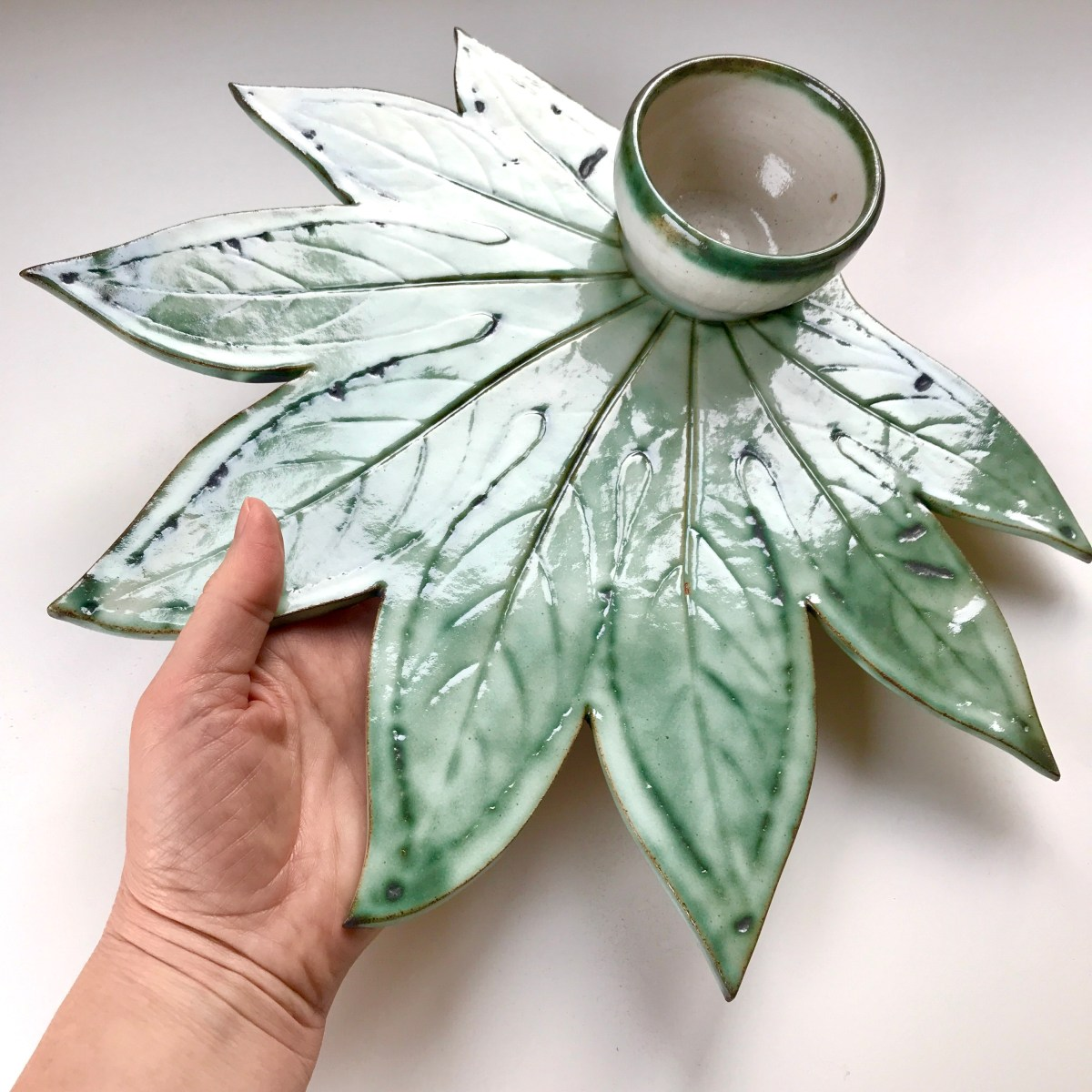 Fatsia Leaf Sharing Platter & Condiment Bowl by Sonya Ceramic Art (size context with hand)