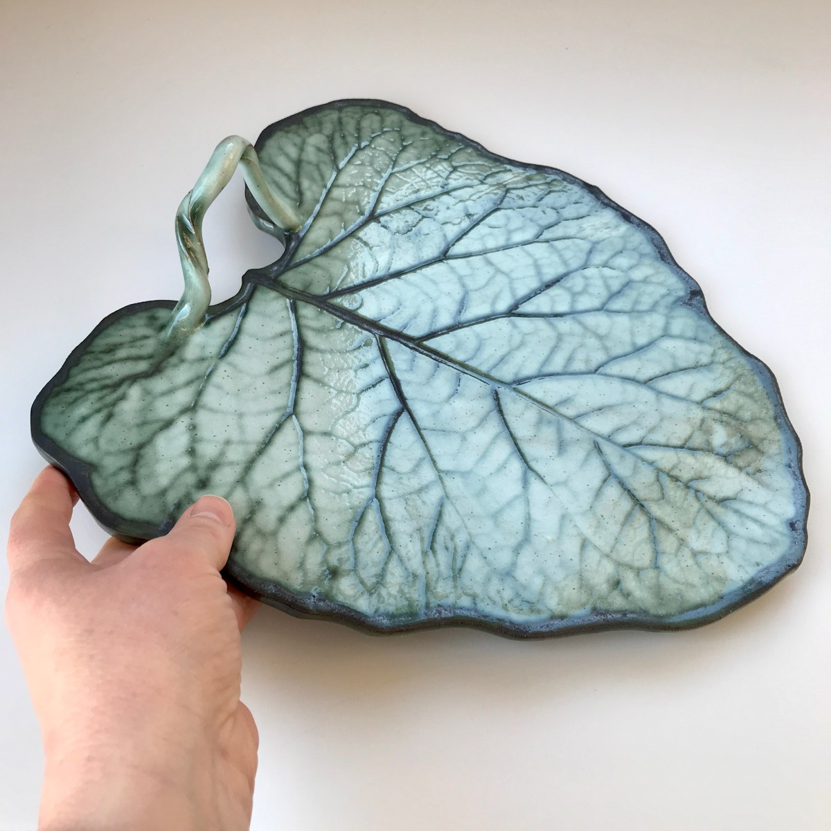 Burdock Leaf Sharing Platter by Sonya Ceramic Art (size context with hand)